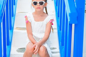 Adorable little girl on the steps at street of typical greek traditional village on Mykonos Island, in Greece