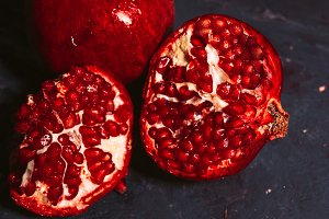 red sliced pomegranate on a blue abstraction background