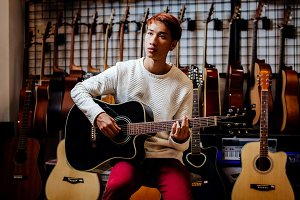 asian man playing acoustic guitar