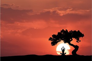 Silhouette of a sitting woman practicing yoga