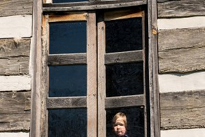 Lonely small baby girl behind window