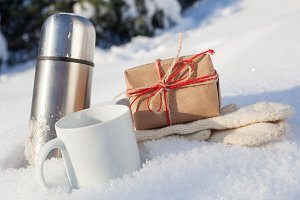 box with cup and mittens in snow