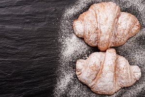 two croissant sprinkled with powdered sugar on black stone background with copy space for your text. Top view