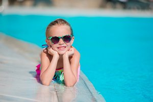 Little happy girl enjoy vacation in outdoor swimming pool