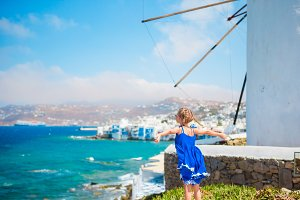 Happy little girl in front of windmills at popular tourist area on Mykonos island, Greece