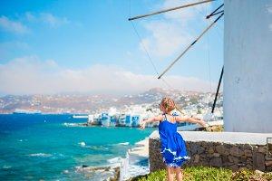 Happy little girl in front of windmills at popular tourist area on Mykonos island, Greece