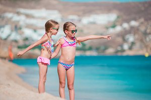 Adorable little girls enjoy summer beach vacation