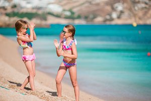 Adorable little girls having fun on summer beach vacation