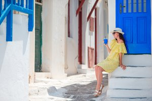 Woman drinking cold coffee to go in outdoors in hot summer day