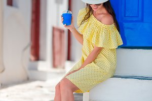 Beautiful woman with coffee to go outdoor in old greek streets