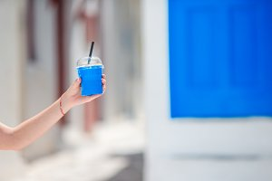 Closeup cold coffee to go in outdoors in hot summer day