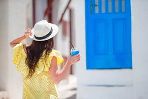 Woman with coffee to go in greek village outdoors. Young girl with cold drink outdoor in hot day