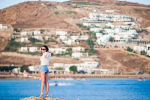 Young happy woman on the edge of a cliff with amazing view of old small village in Mykonos, Greek