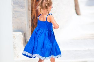 Adorable little girl at street of typical greek traditional village on Mykonos Island, in Greece