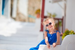 Adorable little girl at street of greek old village on Mykonos Island, in Greece