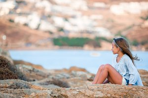 Adorable little girl in Greece in the evening background beautiful landscape