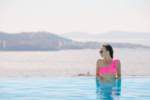 Happy girl relaxing on the edge of pool with amazing view on Mykonos, Greece