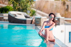 Young happy beautiful woman enjoying summer vacation onthe edge of pool, sunbathing, outdoor portrait