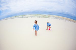 Adorable happy little girls have fun at shallow water on beach vacation