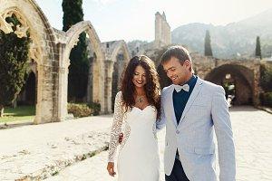 Happy newlyweds walk around a park