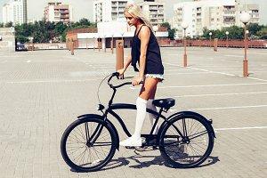 beautiful blonde head woman on bike in city