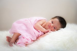 Newborn girl lying happy and relaxed on a white hair blanket