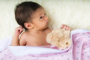 Happy newborn girl whit her teddy
