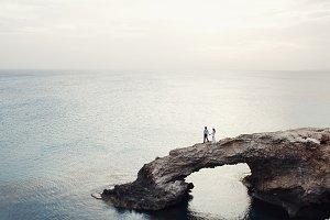 Wedding couple walks over a bridge