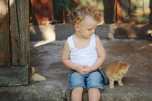 photo of young boy with red kitten