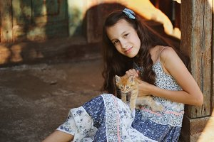 photo of young girl with red kitten