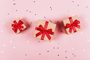Three presents with red bow on pink