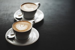 Two cups of cappuccino on black table