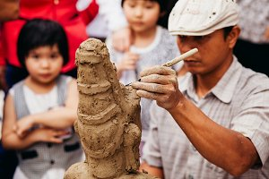 vietnamese sculptor man with clay