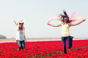 women jumping in a red tulip field