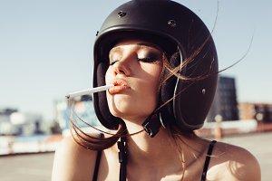 Close-up of Beautiful smoking girl in helmet