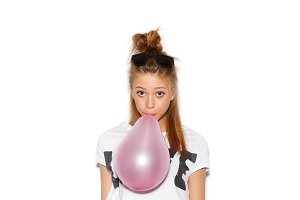 woman blowing a pink balloon
