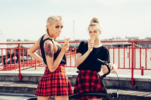 two sensuality young beautiful girls eating ice-cream