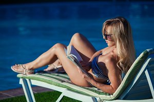 Girl is sunbathing and reading a book by the swimming pool. She is wearing a beautiful swimsuit and pretty sunglasses