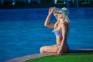 Beautiful young woman is sitting on ledge of swimming pool and looking away.