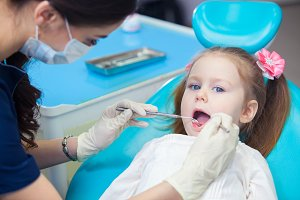 Close-up of pretty little girl opening his mouth wide during inspection of oral cavity at the dentist