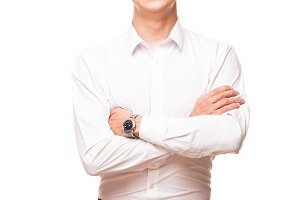 Young handsome businessman in white shirt is standing straight and crossing his hands, portrait isolated on white background