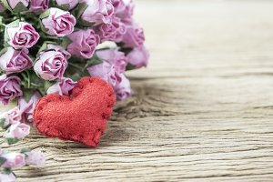 Pink rose with heart on old wood