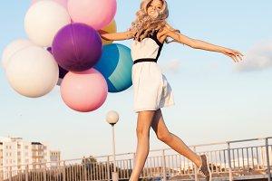 girl walking with big latex balloons