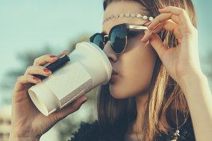 woman in sunglasses drinking coffee