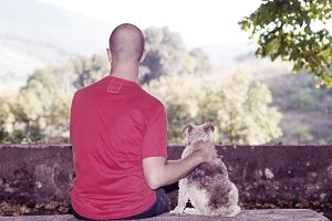 Man with a fox terrier dog sitting