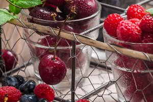 small glasses of fruit containing cherry, blueberry and rasberry