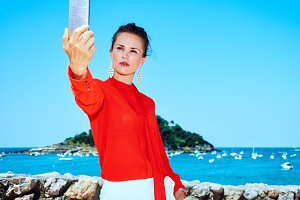 tourist woman in Donostia, Spain with smartphone taking selfie