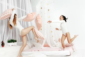laughing girls having pillow fight on the bed