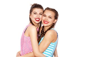 Two fashion laughing girl friends hugging and having fun