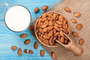 Almond milk in a glass and almonds in a bowl on blue wooden background. Top view